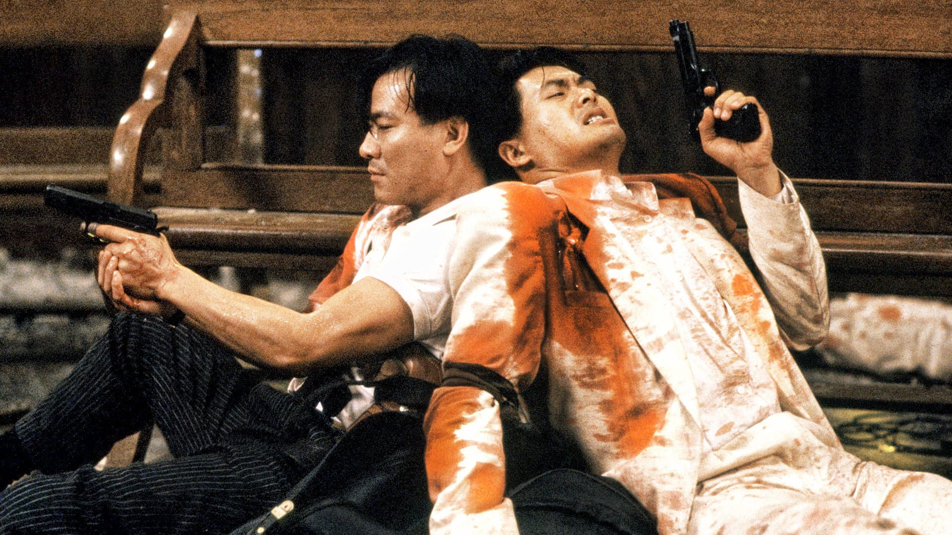 Two men sitting on the floor, holding guns back to back