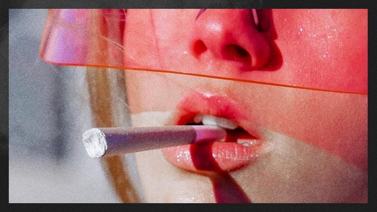 A girl wearing a pink visor with a pre-rolled joint hanging from her mouth