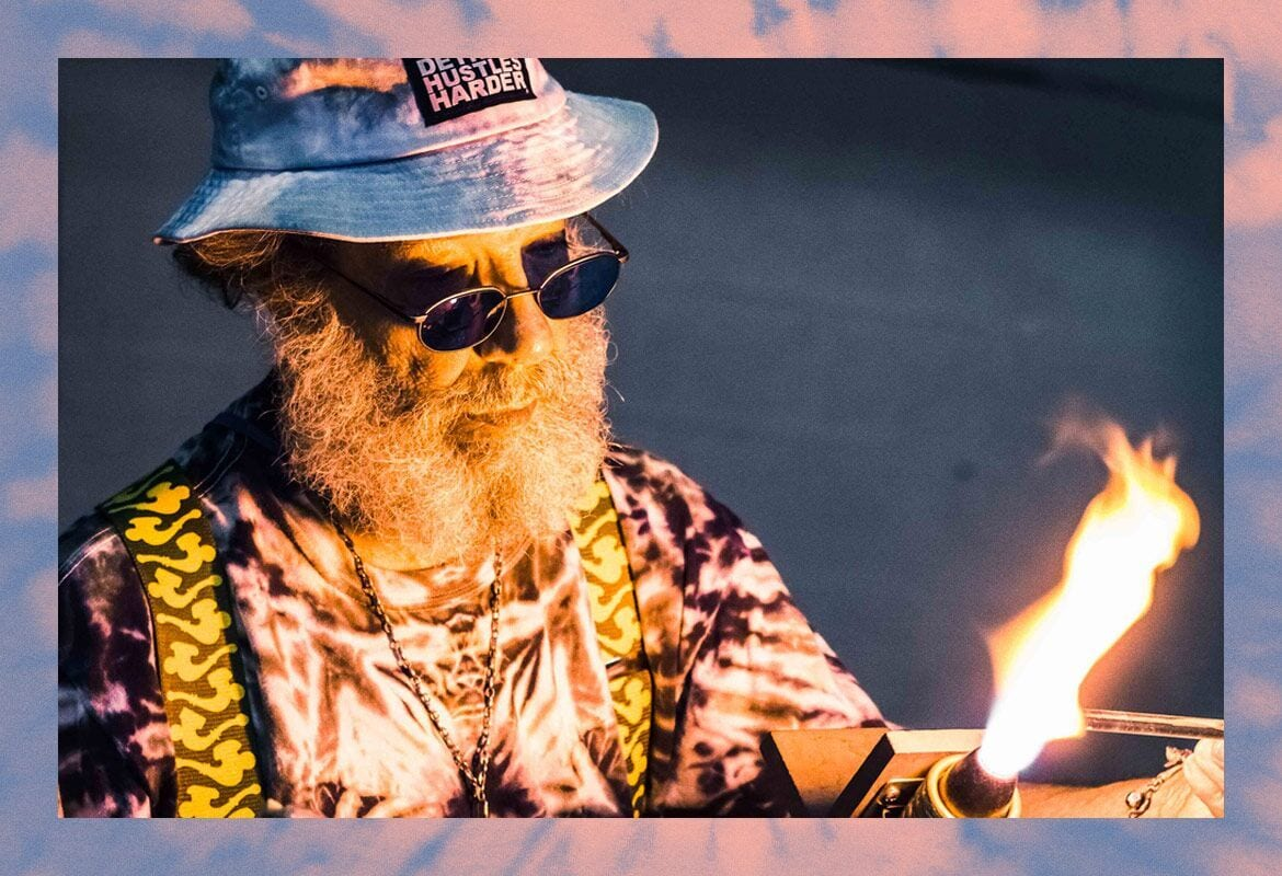 An old man glass blowing in hippie clothing